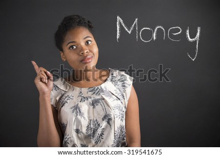 South African or African American black woman teacher or student with a good idea or answer about money standing against a chalk blackboard background inside