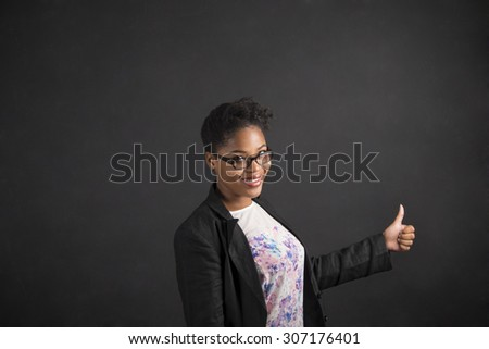 South African or African American black woman teacher or student with a thumbs up hand signal standing against a chalk blackboard background inside - stock photo