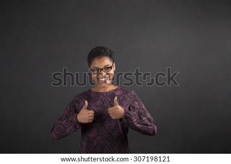 South African or African American black woman teacher or student with a thumbs up hand signal standing against a chalk blackboard background inside