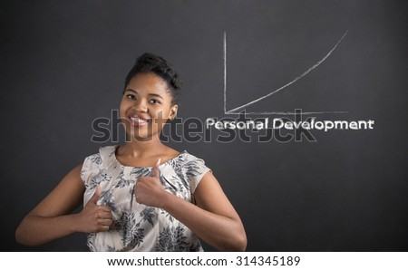 South African or African American black woman teacher or student with a thumbs up hand signal personal development graph standing against a chalk blackboard background inside - stock photo