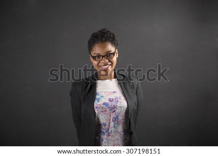South African or African American black woman teacher or student with her arms behind her back on chalk black board background inside