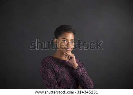 South African or African American black woman teacher or student with her hand on her chin whilst thinking standing against a chalk blackboard background inside