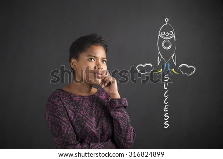 South African or African American black woman teacher or student with her hand on her chin whilst thinking about success rocketing standing against a chalk blackboard background inside - stock photo
