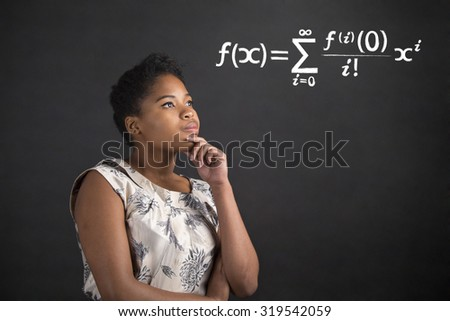 South African or African American black woman teacher or student with her hand on her chin whilst thinking about maths standing against a chalk blackboard background inside - stock photo