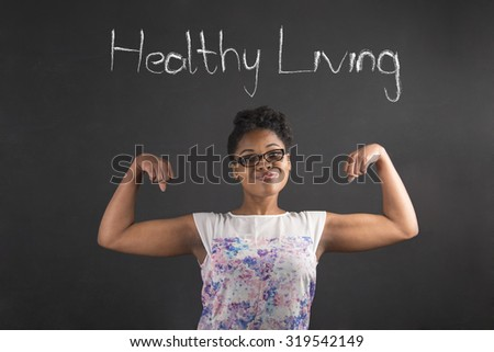South African or African American black woman teacher or student with strong muscular arms healthy living standing against a chalk blackboard background inside