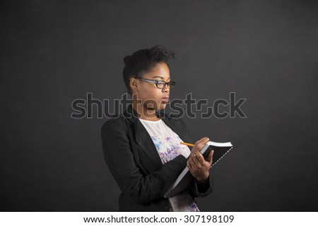South African or African American black woman teacher or student writing in a book or diary against a chalk blackboard background inside