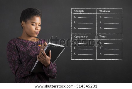 South African or African American black woman teacher or student writing in a book or diary SWOT analysis against a chalk blackboard background inside