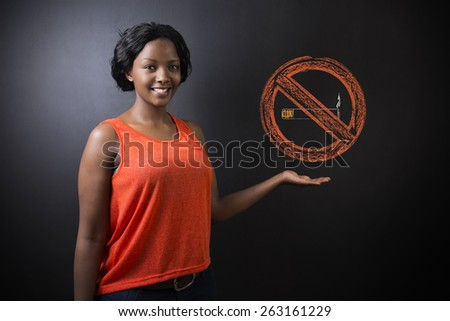 South African or African American woman teacher or student displaying a no smoking sign - stock photo