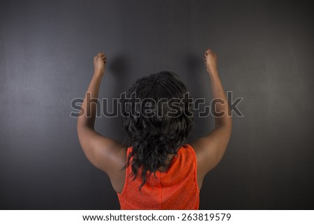 South African or African American woman teacher or student holding fists up on blackboard background - stock photo