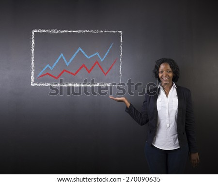 South African or African American woman teacher or student holding hand out standing against a blackboard background with a chalk growth line graph - stock photo