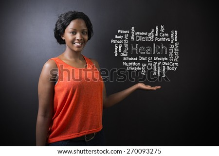 South African or African American woman teacher or student standing with her hand out against a blackboard background with a chalk health diagram - stock photo