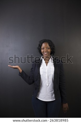 South African or African American woman teacher or student with hand out on chalk black board background - stock photo