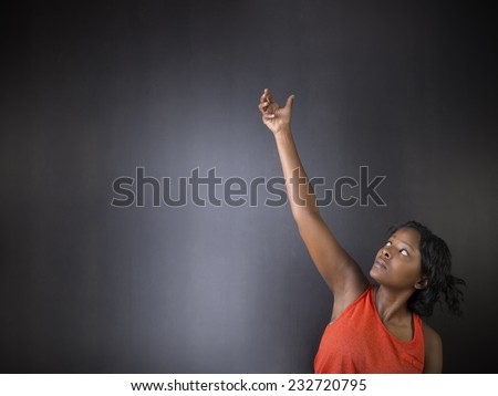 South African or African American woman teacher or student with hand reaching up on chalk black board background - stock photo