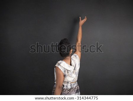 South African or African American woman teacher or student with hand reaching up on chalk black board background inside - stock photo