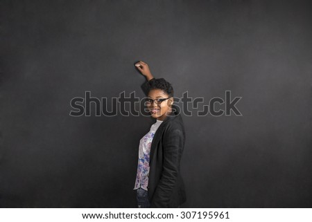 South African or African American woman teacher writing on chalk black board background - stock photo