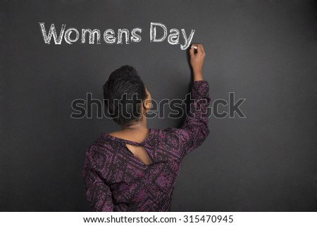 South African or African American woman teacher writing Women's Day on chalk black board background inside