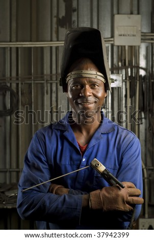 South African or American black worker welder in factory - stock photo