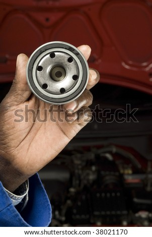 South African or American blue collar mechanic hand with oil filter service car maintenance