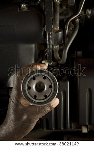 South African or American hand holding oil filter with modern car engine background - stock photo
