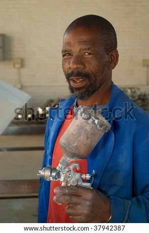 South African or American industrial, worker, handyman painter with spray gun - stock photo
