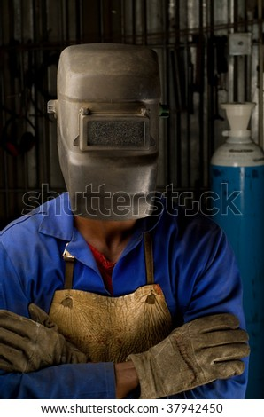 South African or American welder worker wearing saftey mask - stock photo