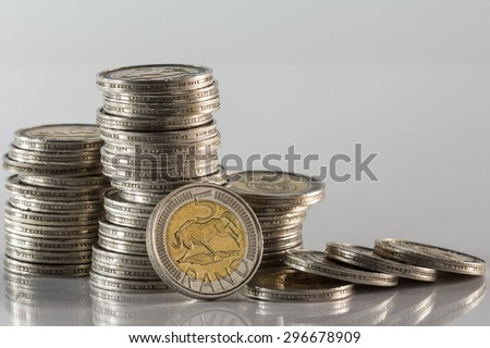 south african silver minted coins in a pile with fallen currency against a white background - stock photo