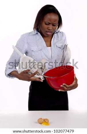 South African woman struggling with a mess she made in the kitchen. - stock photo