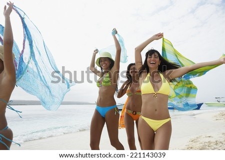 South American women running on beach - stock photo