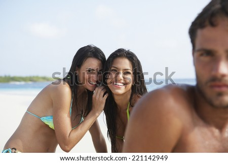 South American women whispering behind man - stock photo