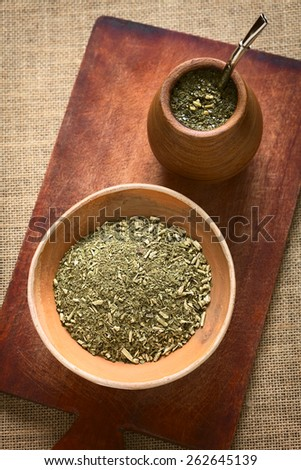 South American yerba mate (mate tea) dried leaves in clay bowl with a wooden mate cup filled with tea photographed with natural light. Mate is the national infusion of Argentina.   - stock photo