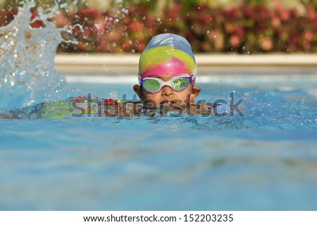 South Asian Indian boy in the swimming pool with goggles in Arab resort - stock photo