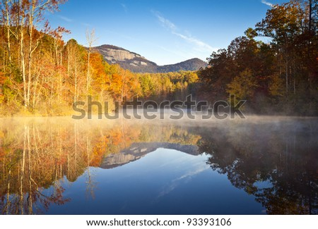 South Carolina Autumn Sunrise Landscape Table Rock Fall Foliage Reflections fog covered lake - stock photo