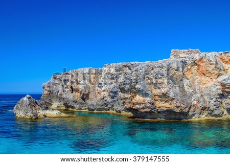 South coast cliff of Menorca island with small ancient talayot surrounded with azure Mediterranean sea water, Balearic Islands, Spain. - stock photo