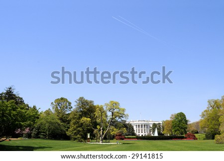 South facade and South lawn of the White House in Washington DC in spring colors, with paths of two airplanes crossing high up in the sky, and ample copyspace in the sky - stock photo