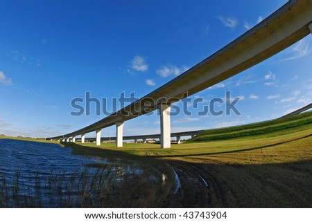 South Florida expressway over lake with blue sky.