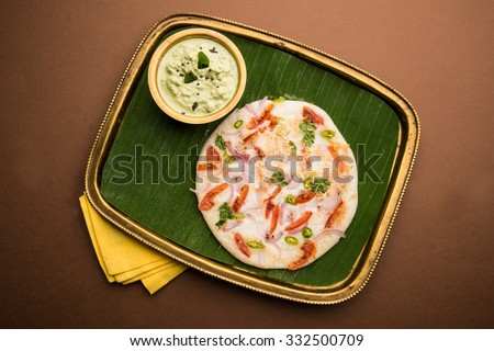 south indian favourite food Uttapam, served over banana leaf in brass tray with coconut chutney on brown background, isolated and top view - stock photo