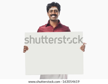 South Indian man holding a blank placard