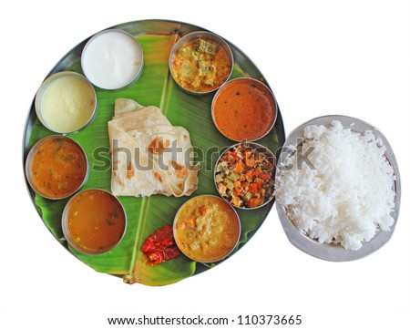 South indian plate meals on banana leaf isolated on white. Traditional vegetarian wholesome indian food with variety of curries, rasam, sambar, rice, subzi and chapatti(chapathi) or roti(phulka). - stock photo