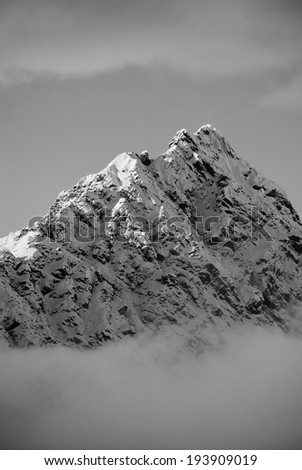 South Island, New Zealand. The tip of a mountain peaks through the clouds. - stock photo