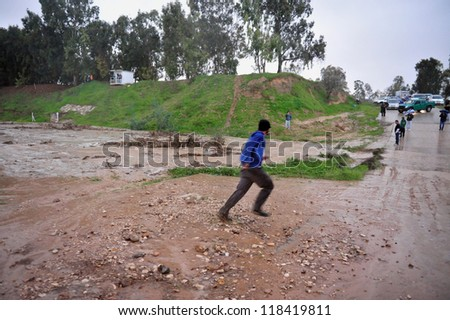 SOUTH ISRAEL - JANUARY 18 2010: A man is crossing at the last moment before a flesh flood hits Nahal Habsor, Israel. Flash floods in Israel are deadly people are killed by them each year - stock photo