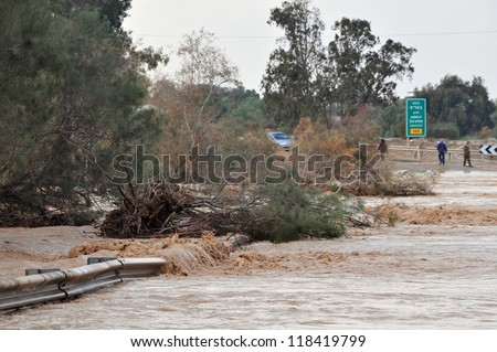 SOUTH ISRAEL  -JANUARY 18: People and cars are  stuck in a  a flash flood on January 18 2010  in Nahal Habsor, Israel.Flash floods in Israel are deadly people are killed by them each year - stock photo