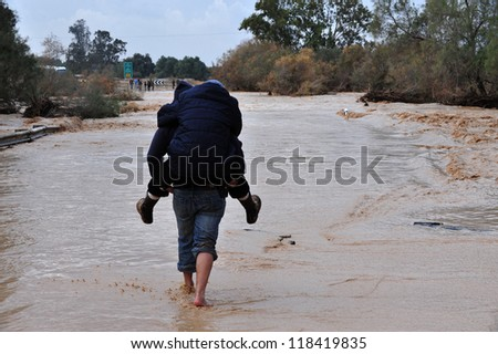 SOUTH ISRAEL - JANUARY 18: Travelers are trying to cross a flash flood in Nahal Habsor Israel, on January 18 2010 .Flash floods in Israel are deadly people are killed by them each year - stock photo