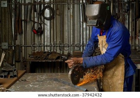 South or African American working with angle grinder - stock photo