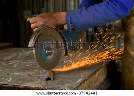 South or African American working with angle grinder