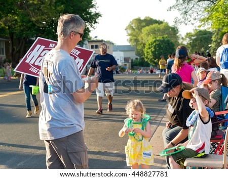 SOUTH ST. PAUL, MINNESOTA - JUNE 24, 2016: Campaign worker hands out literature of local candidates for Minnesota Legislature at annual South St. Paul Kaposia Days Grande Parade on June 24.  - stock photo