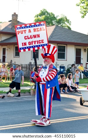 """SOUTH ST. PAUL, MINNESOTA - JUNE 24, 2016: Clown entertains crowd holding sign """"Put a Real Clown in Office"""" at annual South St. Paul Kaposia Days Grande Parade on June 24.  - stock photo"""