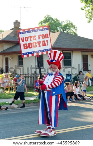 """SOUTH ST. PAUL, MINNESOTA - JUNE 24, 2016: Clown entertains crowd holding sign """"Vote for Booya"""" at annual South St. Paul Days Grande Parade on June 24.  - stock photo"""