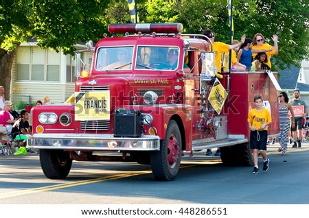 SOUTH ST. PAUL, MINNESOTA - JUNE 24, 2016: Supporters of candidates for city offices in South St. Paul hold banners and wave to crowd from fire truck at annual Kaposia Days Grande Parade on June 24.  - stock photo