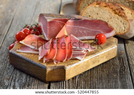 South Tyrolean bacon with fresh stone oven baked bread on a wooden table