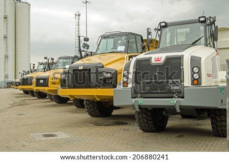 SOUTHAMPTON, UK - MAY 31, 2014: A row of new CAT articulated trucks, made by Caterpillar at the dockside in Southampton, Hampshire.  The port is an important export area for vehicles in the UK.